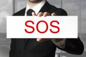 Businessman holding sign sos — Stock Photo