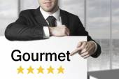 Businessman pointing on sign gourmet five star rating — Stock Photo