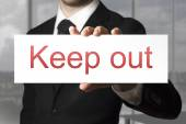 Businessman holding sign keep out — Stock Photo