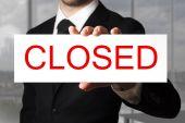 Podnikatel drží ceduli zavřeno — Stock fotografie