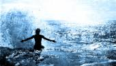 Ocean Wave Splashing on a Man sitting on a cliff — Stock Photo