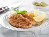 Chicken or pork schnitzel with lemon wedges — Stock Photo