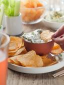 Potato chips and fresh vegetables with dip — Stock Photo