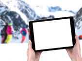 Tablet in hands and people skiing in the background — Stock Photo