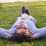 Businessman lie down on the grass ground — Stock Photo #58026151