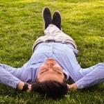 Businessman lie down on the grass ground — Stock Photo #58026297