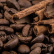 Coffee beans with cinnamon sticks on sack textile — Stock Photo #65831755