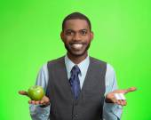 Man holding apple in one hand, pills, vitamins in another — Stock Photo