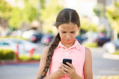Unhappy girl reading text message on smart phone — Stock Photo