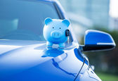 Piggy bank and key on a car hood — Foto de Stock
