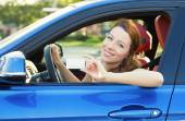 Woman in new car showing blank drivers license — Stock Photo