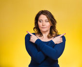 Confused young woman pointing with fingers in two different directions — Stockfoto