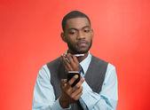 Man shaving, using trimmer, reading news on smartphone — Stock Photo
