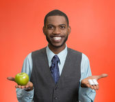 Man holding green apple in one hand, pills, vitamins in another — Stock Photo