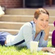 Female student lying down on lawn grass working on laptop — Stock Photo #52576447