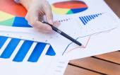 Female hands pointing with pen at business financial report graphic — Stock Photo