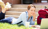 Female student lying down on lawn grass working on laptop  — Stock Photo