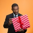 Surprised businessman about to open unwrap red gift box — Stock Photo #52710135