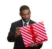 Surprised businessman about to open unwrap red gift box — Stock Photo
