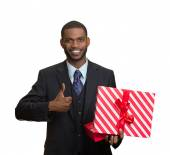 Smiling business man holding present, giving thumb up — Stock Photo