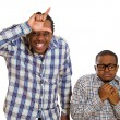 Two men, rude bully showing looser sign, shy little nerdy guy  — Stock Photo #52765663