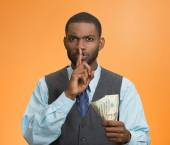 Corrupt businessman holding dollar bills in hand showing shhh sign — Stock Photo