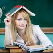 Student sitting at desk in classroom looking upwards, confused, thinking — Stock Photo #52786463