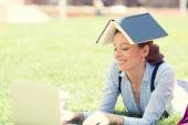 Young female student using laptop outdoor — Stock Photo