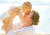 Happy grandmother smiling baby grandson, head to head isolated lake, sea background — Stock Photo