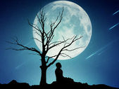 Silhouette of a meditating man on moonlight sky background — Stock Photo