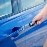 Women's hand presses on remote control unlocks car door — Stock Photo #53615177