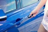 Women's hand presses on remote control unlocks car door — Stock Photo