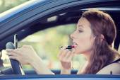 Young woman applying makeup while driving car — Stock Photo