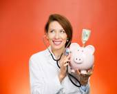 Doctor listening with stethoscope to piggy bank — Stock Photo