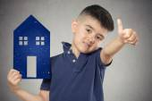 Child holding paper house showing thumbs up — Stock Photo