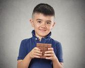 Boy eating whole bar of chocolate — Stock Photo