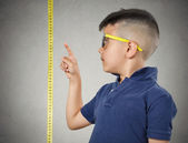 Child pointing at his height on measuring tape — 图库照片