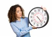 Woman, worker, holding clock looking anxiously, pressured by lack of time — Stockfoto