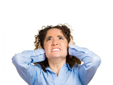 Stressed woman covering her ears, looking up