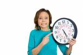 Senior woman holding clock looking anxiously pressured by lack of time — Foto de Stock