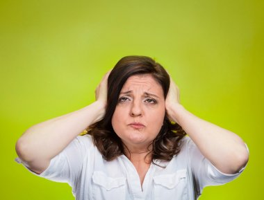 Unhappy stressed woman covering ears looking up