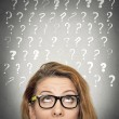 Woman with puzzled face expression and question marks above head — Stock Photo #54269911