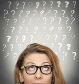 Woman with puzzled face expression and question marks above head — Stock Photo