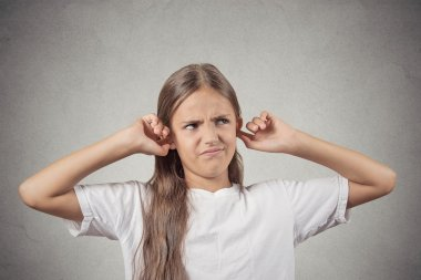 Annoyed girl covering her ears loud noise upstairs