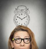 Business woman with alarm clock above her head — Stock Photo