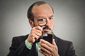 Man looking through a magnifying glass on smartphone — Stock Photo