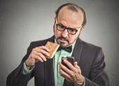 Man reading message on smart phone eating cookie  — Foto de Stock