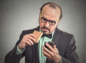 Man reading message on smart phone eating cookie  — Stok fotoğraf