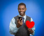 Man looking at smart phone holding red heart — Stock Photo