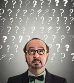 Man puzzled question marks above head — Stockfoto